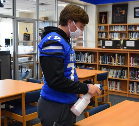 Senior library aide, Alec Burdge helps maintain clean surfaces for students using the library  throughout the day.